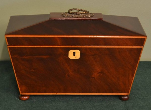 A Regency mahogany antique tea caddy, such as this one—dating from around 1820 with a canted lid with decorative brass handle and boxwood string inlay—revealed a hidden compartment and hints to a tragic story.