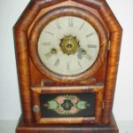 This pine and Rosewood-veneer clock with a painted glass door is a typical New Haven Clock Company cottage clock.