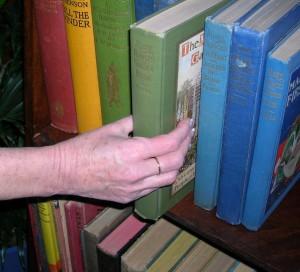 Sliding a book off of a shelf.