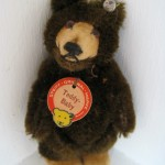 "This precious 9-cm Teddy Baby is from my personal collection; he is five ways jointed, deep chocolate brown, and has his signature tan velvet muzzle with a closed mouth and flat, broad feet. The 9-cm did not have the red leather collar. He is in pristine condition with his Steiff ""raised script button"" or RSB, crisp chest tag, and even his white linen ""US Zone"" tag stitched into his back seam. He dates from the very early 1950s."