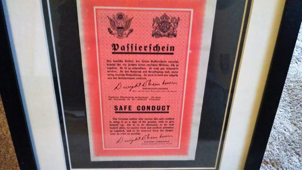 "This small read leaflet, mounted nicely in a glass frame, was dropped by the Allies to warn citizens before an invasion, offering them safe passage or ""Safe Conduct."""