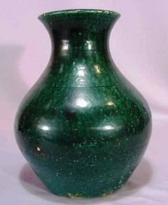 This nice and early vessel, made by J.B. Cole, has a flaring form and is covered in a lead green glaze.