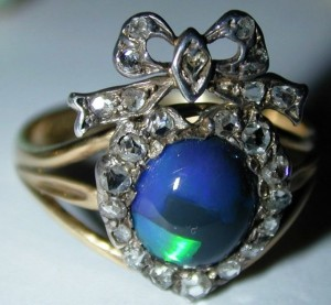 A stunning Victorian black opal ring in a heart and bow setting of 18K yellow gold and silver.