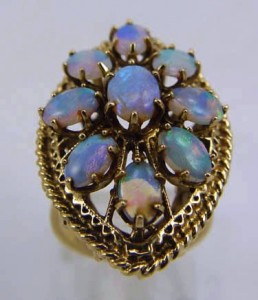 This large and spectacular vintage opal ring is finely crafted in solid 14K yellow gold. The center opal measures 7mm x 5mm, and surrounding gems are 6mm x 4mm each. The total weight for these colorful gems is about 2.71 carats.