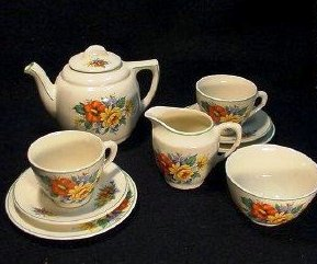 A 9-piece child's tea set with a floral pattern and bright colors with green banding produced in England under the conditions set by the British Board of Trade.