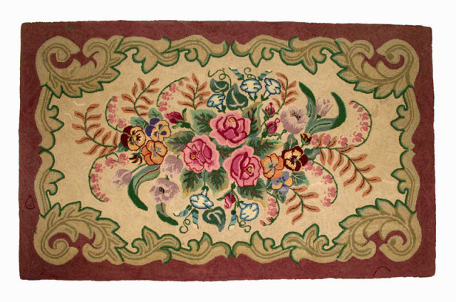 Traditional floral bouquet framed by scrolling leaves, finely hand hooked, wool on burlap, circa 1940, circa 1940.