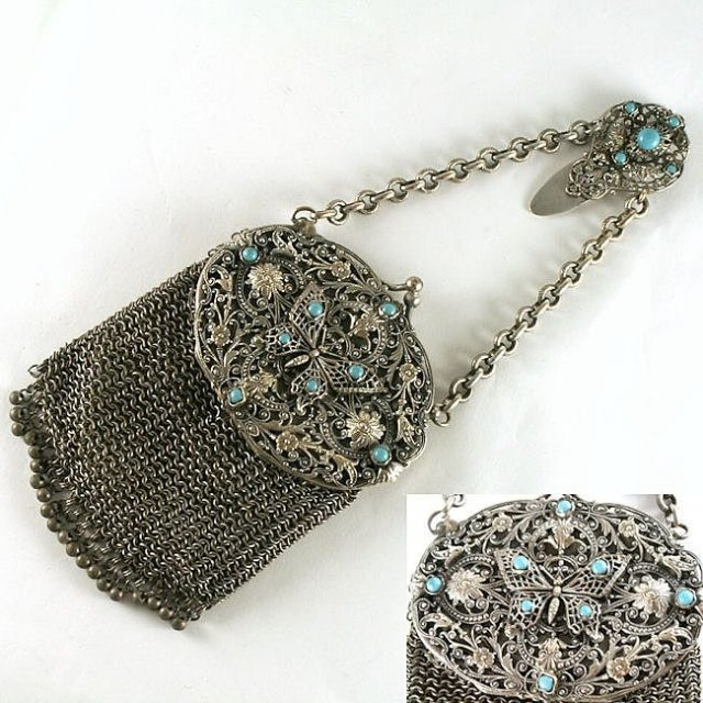 This châtelaine chain mail purse has dangling steal beads on the bottom for various attachments and an interior mirror with the original green silk liner. A silver filigree top features a matching belt clip that also has Turquoise beads. Circa 1850.