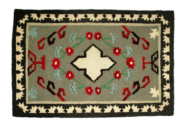 A hooked rug with a geometric pattern, which appears to be inspired by Native American design, circa 1930.