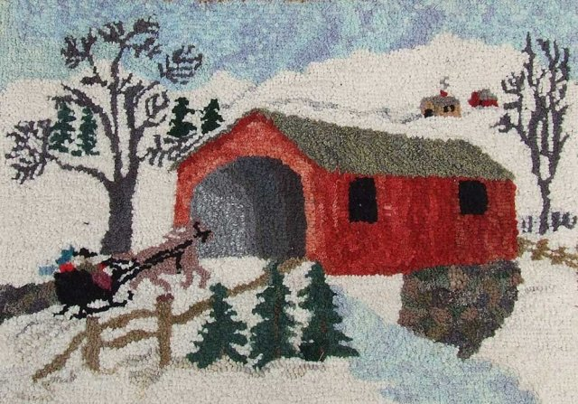 "A vintage hooked rug made by Pearl McGown depicting a New England scene of snow covered landscape with a horse pulled sleigh approaching a red covered bridge, made of wool on a burlap base. The inscription on the burlap reads: ""May the simple joys of life be yours this Christmas – 1951- Pearl M McGown F25."""