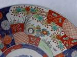 An Imari porcelain plate with old repairs and rim chips that are easily visible to the naked eye.