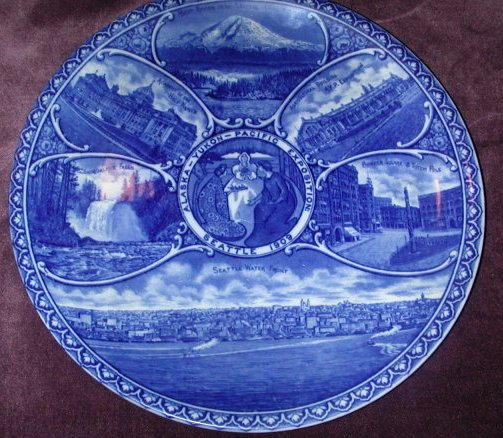 An example of a Rowland & Marsellus Co. Alaska-Yukon-Pacific Exposition commemorative blue transferware plate, ca. 1909. The exposition was held in Seattle in 1909 and the face decoration depicts various Seattle and area landmarks.