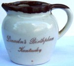 "A souvenir pitcher from ""Lincoln's Birthplace Kentucky."" The pitcher is 3 inches high and marked ""PCA, Hand crafted, made in USA"" on bottom."