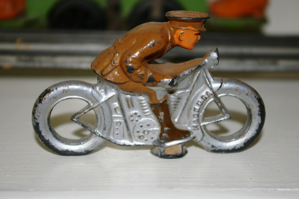 A toy soldier riding a motorcycle made by Barclay, one of the original American toy soldier manufacturers.