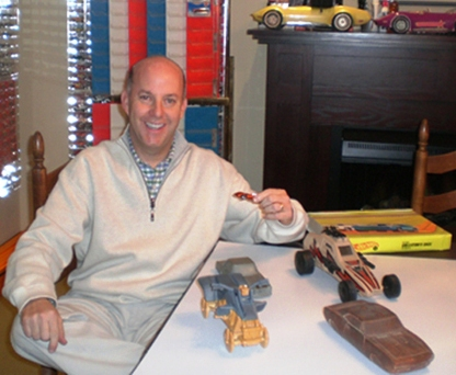 Bruce Pascal poses with orange Ferrari P917 Hot Wheels and prototype Hot Wheel molds