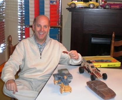 Bruce Pascal poses with orange Ferrari P917 Hot Wheels and prototype Hot Wheel molds