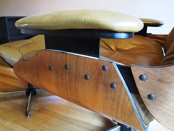 Charles and Ray Eames were looking for a seamless look, without any visible hardware. The real chair is held together with rubber shock-mounts glued to the wood under the cushions. If you see screws, it's a knock-off.