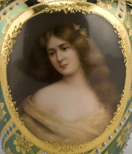 A close-up of the hand-painted portrait of a Victorian woman with rosy cheeks and flowing hair.