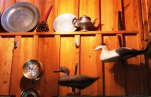 These decoys are mounted on the wall using hand forged iron L brackets. The decoy on the left is a Mitchell Black Duck and the black and white decoy is an Eider from Maine. Also on the cypress board and batten wall is a Chelsea clock and barometer with a pewter collection on the shelf above.