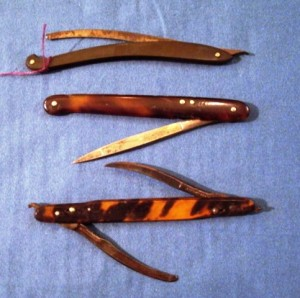 This style of folding scalpel was in use throughout the 19th century. The curved one at the top is an earlier curved-style with horn handle, while the tortoiseshell-handled scalpels are of a later, straight design. The double scalpel at the bottom is actually two bistouries. Bistouries are scalpels with longer, thinner blades that can be curved or straight.
