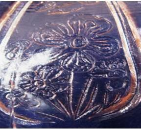 Two views of reproduction Cherry Blossom butter dish lid panel. The flowers look like a child's drawing.