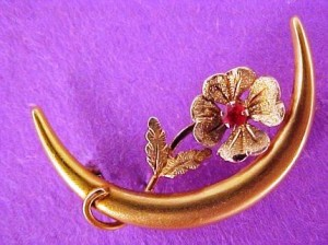 An early Victorian Honeymoon pin 10k yellow-gold with a tiny genuine ruby prong set in middle of flower.