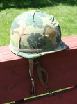 A 1967 dated US M1-C paratrooper helmet w/ cloth camouflage cover.