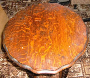 This turn-of-the-century oak table top sure looks-well worn by long handling – and abuse. It still probably qualifies as having patina.