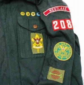 "This green long-sleeved Boy Scout shirt, dating from the 1954, displays several patches and pins, including a Westlake ""red and white"" council name patch, a key and a wheel patch, a rank patch and service pins."