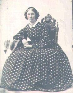 Early 1860s plain dress with large, round hoop, buttons down the front, tight cuffs and a tiny white collar.