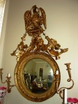 Anglo-American giltwood convex looking glass mirror in the Regency style, circa 1800-1825 ($9,900).