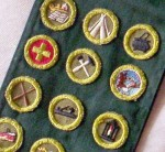 A collection of 1950s-vinatge Boy Scout merit badges on a sash, including Reading, Camping, Cooking, First Aid, Home Repair, World Brotherhood, Canoeing, Carpentry, Metalwork.