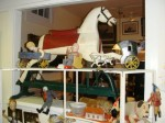 A hobby horse from the 19th century on a sliding base, surrounded by many collectible toys, will be sold.