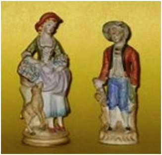 Two Bisque figurines painted in muted colors.