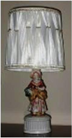 A glazed porcelain table lamp showing a well-dressed girl, 9 inches tall. The shade is in the 1950s style, but is probably not original to the lamp.