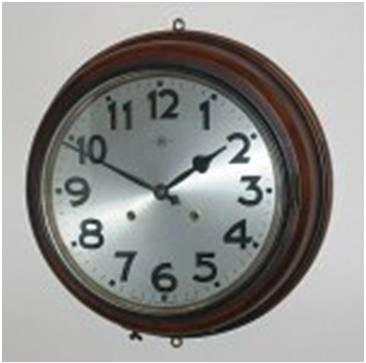 "An example of a fine-quality wall clock that strikes on the hour and half-hour, with a 15-inch overall diameter. The maker's logo is a capital ""H,"" just below the 12, while the printed ""MIOJ"" is below the 6."