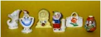 Porcelain miniatures, standing 2 ½ inches tall, of a shell, dancing girl, clock, toothpick holder, bag and Oriental vase.
