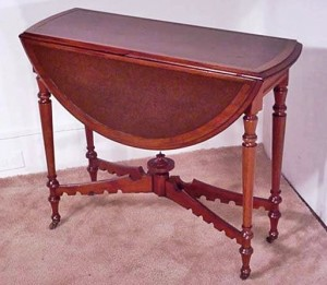 This may look like an ordinary drop leaf table, but it has a unique mechanical feature. The table was originally designed for card or game playing. This card table has an inset leather top. When the leaves are down, it only measures 12 and a half inches wide. By raising both leaves at the same time, two legs are spring-loaded and automatically swing out to support the leaves. Circa 1880.