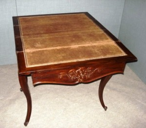 A 19th-century rosewood fold-over continental card table, standing on slender cabriole legs, with carvings to the toes. The table is fitted with carved center drawer, fitted with a lock and key. The open top is lined with brown baise.