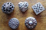 Vintage metal button covers featuring filigree flower in silver tones, circa 1940.