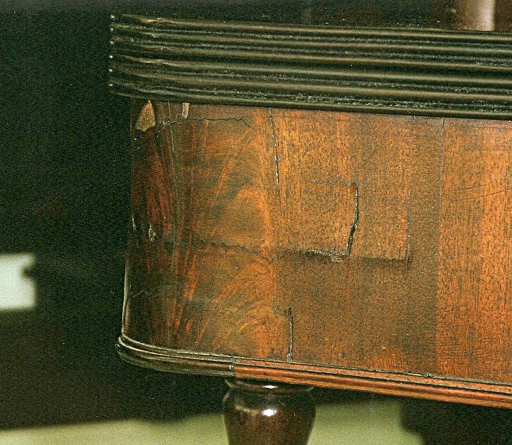 In this photo the solid wood underlayment has shrunk under the veneer of the skirt of this Federal era fold over game table telegraphing the damage to the surface.