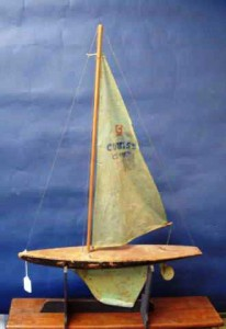 This is a manufactured pond boat made by Curtiss, called the Curtiss Cutter. It is cutter rigged and has an original plastic sail and metal keel and rudder. It is 19 inches long and 29 ½ inches tall, with a solid body construction and a flat deck. It was made mid-20th century. Value in a retail setting is about $100.