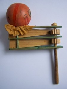 A German wood ratchet from 1920 with a composition pumpkin head and crepe paper collar. The ratchet makes a loud scraping noise when twirled.