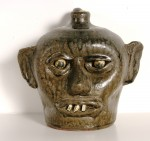 Hand-turned china plate teeth face jug by Lanier Meaders, crafted in 1968, with tobacco-split glaze.