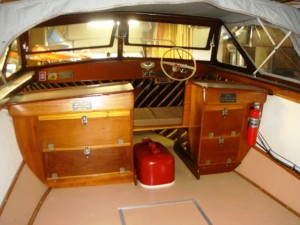Interior view of a white 1966 wooden Grady White motorboat with trailer, in excellent condition.