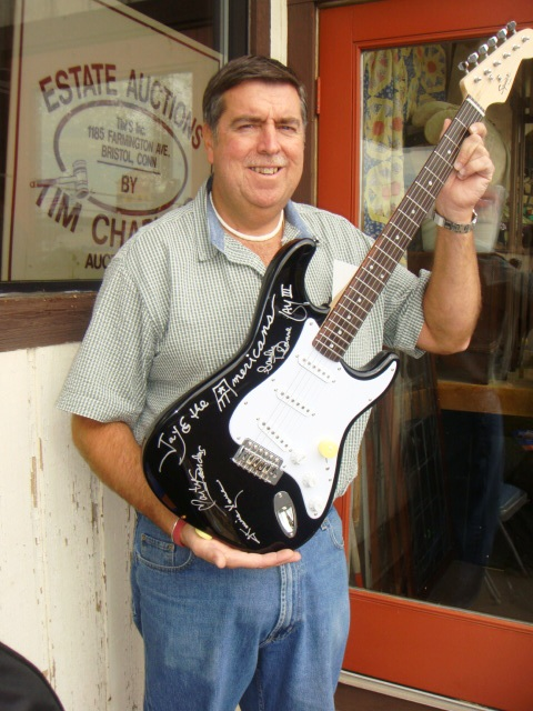 Auctioneer Tim Chapulis with a guitar signed by the members of the rock group Jay & the Americans, just one of several pieces of rock 'n' roll memorabilia items to go up for auction to benefit the Litchfield Firehouse.