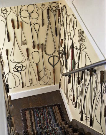A collection of vintage rug beaters are displayed on the walls of the staircase. Don't constrict where you display your collections by sticking to shelves.