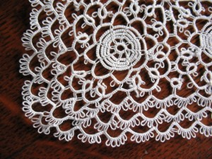 Close-up of the handkerchief showing the intricate detail of the tatting. The round loops on the edge of the chain are picots, which are typical of tatting.