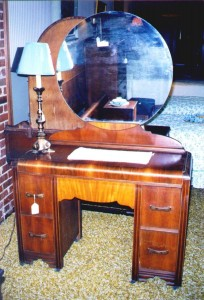 A very plain Art Moderne vanity having only its hardware, round mirror and waterfall to announce its style.