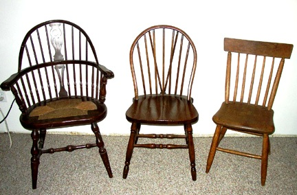 "These chairs are (left to right) are a hoop-back or sack-back, a hoop-back or loop-back and a fan-back or rod-back. The sack back with the solid splat is American made but it is a Depression era reproduction of an English chair. Only English chairs originally had solid splats. The design in the splat indicated the local pub to which it belonged. American Windsors did not have solid splats until the Depression. English Windsors also tend to have very straight vertical legs. American 18th-century Windsors had legs that spayed out more widely. The hoop back chair in the middle is also called a ""brace back"" because of the extra back supports behind the main spindles."