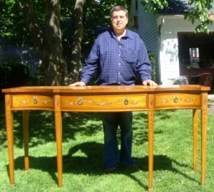 Auctioneer Tim Chapulis with an Edwardian Adams-style satinwood sideboard, ca. 1890-1910.